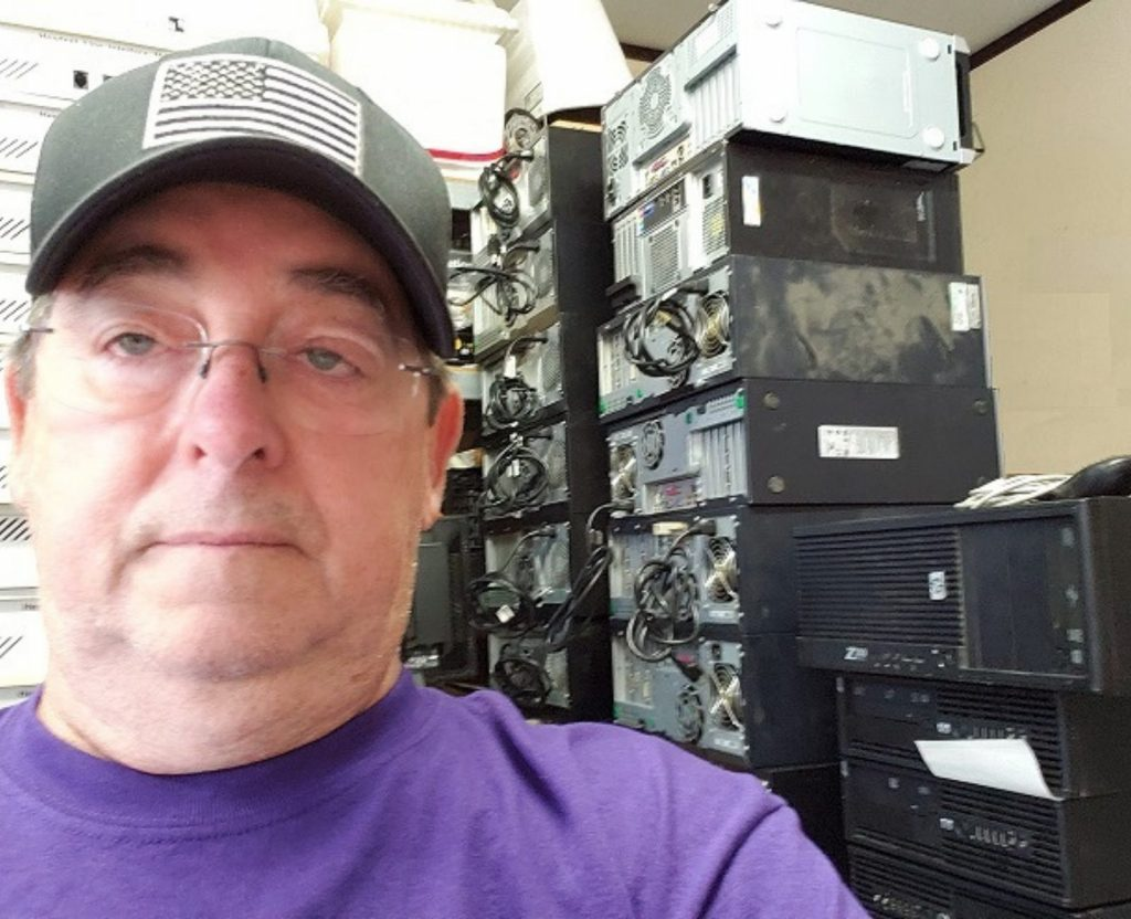 Man sitting in front of computer harddrive stacks.